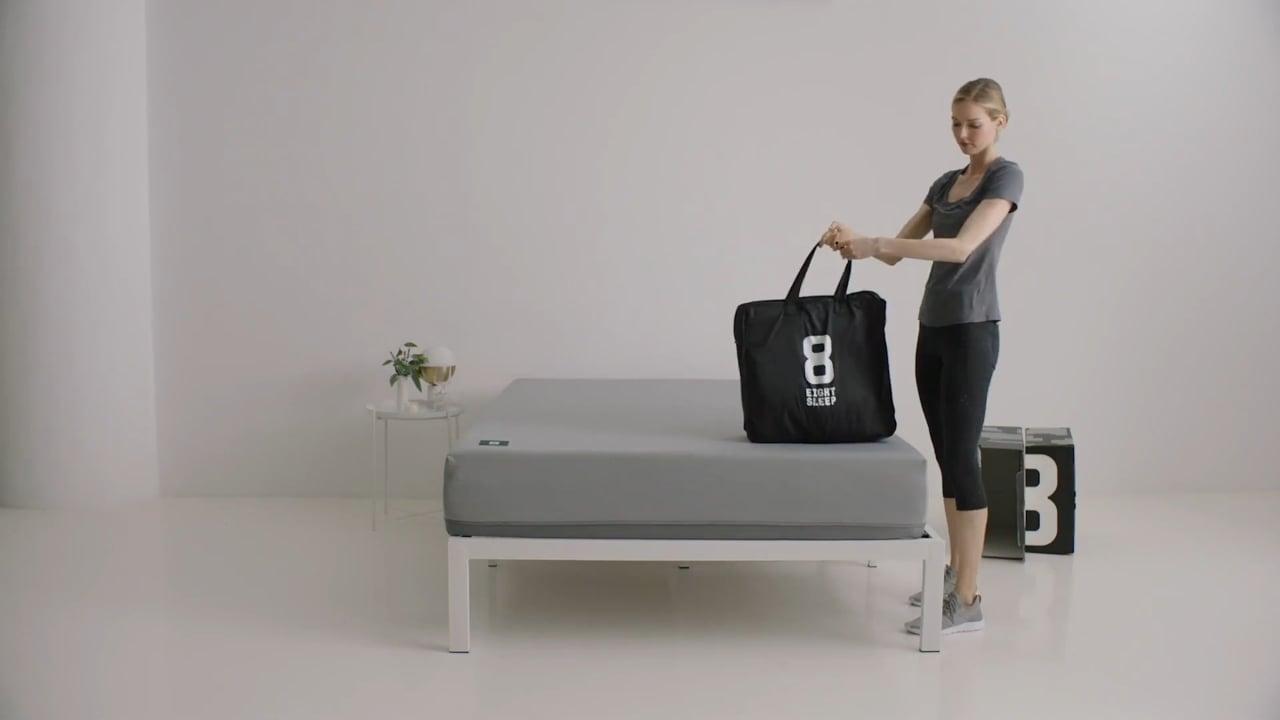 Woman standing near Pod mattress with bag showing Eight Sleep logo